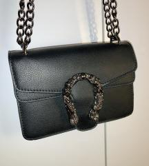 Crna torbica s ukrasnom kopčom