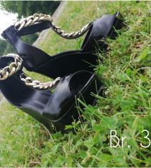 Crne sandale sa zlatnim lancem.